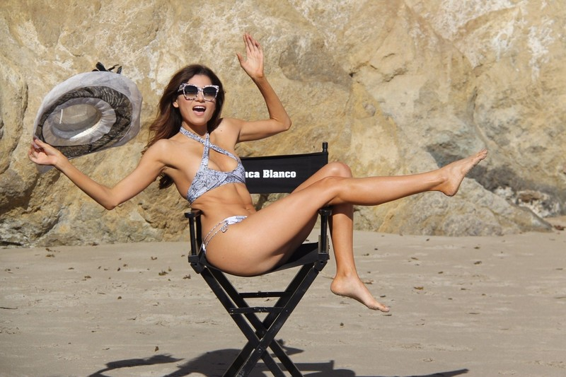 Blanca Blanco wears a bikini while sitting in a directors chair in Malibu