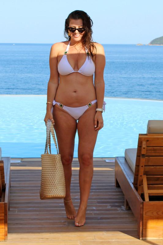 Imogen Thomas sunbathes in a white bikini at an infinity pool by the coast line.